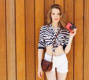 Mulher de sorriso 'sexy' nova do fotógrafo, guardando e fazendo a imagem na câmera retro do vintage, roupa marinha brilhante vest Imagem de Stock Royalty Free