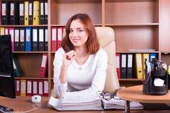 A mulher de sorriso trabalha no escritório Fotos de Stock