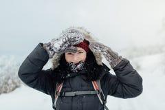 A mulher de sorriso vestiu morno protegendo seus olhos com luvas nevado Fotografia de Stock