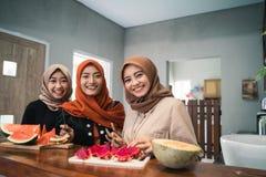 Mulher de tr?s hijab que sorri quando prepare a fatia dos frutos fotos de stock royalty free