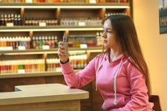 Mulher de Vape Menina bonito nova no hoodie cor-de-rosa que fuma um cigarro eletrônico foto de stock royalty free