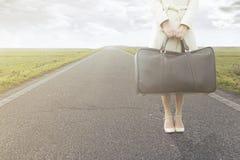 A mulher de viagem espera com sua mala de viagem na borda da estrada imagens de stock