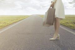 A mulher de viagem espera com sua mala de viagem para sair para uma viagem nova Imagens de Stock Royalty Free