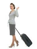 Mulher de viagem feliz com mão de ondulação da mala de viagem Fotos de Stock Royalty Free