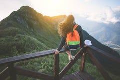 Mulher de viagem nova com a trouxa que senta-se altamente na parte superior da montanha com cabelo de ondulação, nivelando com po fotos de stock royalty free