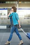 Mulher de viagem que anda com mala de viagem e telefone celular no aeroporto Imagens de Stock Royalty Free