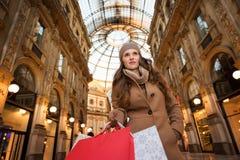 Mulher de Vogue com os sacos de compras na galeria Vittorio Emanuele II Foto de Stock