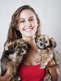 Mulher de Yoing que prende dois filhotes de cachorro Foto de Stock