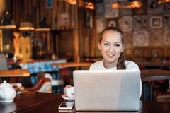 Mulher de Yong um trabalho no portátil no café Foto de Stock Royalty Free