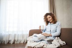 A mulher decidiu tratar-se no bom dia brilhante Retrato do assento fêmea encaracolado-de cabelo fêmea atrativo no sofá dentro Fotos de Stock