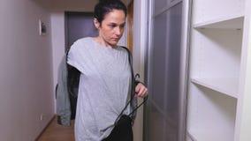 A mulher decola o revestimento de bombardeiro perto do vestuário video estoque