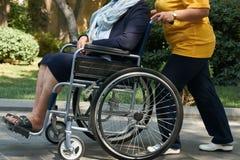 Mulher deficiente em uma cadeira de rodas que relaxa em um parque com um assistente do cuidado fotografia de stock