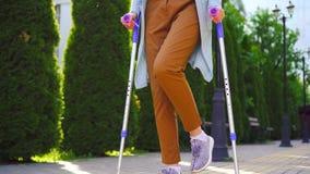 Mulher deficiente irreconhecível com um ferimento em muletas que anda no parque mo lento ensolarado video estoque