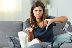 Mulher deficiente irritada que guarda comprimidos com polegares para baixo imagem de stock