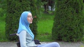 Mulher deficiente nova positiva em um carrinho de criança muçulmano do hijab em uma caminhada no parque filme