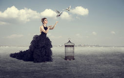 A mulher deixa os pássaros para fora fotografia de stock