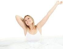 Mulher deleitada que estica o assento em sua cama Fotos de Stock