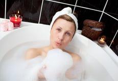 Mulher deleitada que tem o divertimento em um banho de bolha Imagens de Stock