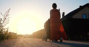 Mulher delgada em um vestido vermelho que monta um bebê em um pram no por do sol fotos de stock
