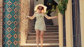 A mulher delgada no vestido de cocktail curto com ombros abertos vai para baixo e toma a foto da recreação vídeos de arquivo