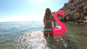 A mulher delgada nova aprecia o mar e o sol que anda na água com um flamingo inflável cor-de-rosa vídeos de arquivo