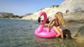 A mulher delgada nova aprecia o mar e o sol que anda na água com um flamingo inflável cor-de-rosa filme