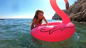 A mulher delgada nova aprecia o mar e o sol que encontram-se em um flamingo cor-de-rosa inflável video estoque