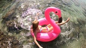 A mulher delgada nova aprecia o mar e o sol que encontram-se em um flamingo cor-de-rosa inflável vídeos de arquivo