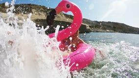 A mulher delgada nova aprecia o mar e o sol que encontram-se em um flamingo cor-de-rosa inflável filme