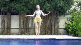 A mulher delgada nova dança uma dança oriental perto da associação no recurso tropical, movimento lento video estoque
