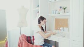 A mulher delgada nova entra a sala e senta-se para baixo em uma cadeira vídeos de arquivo