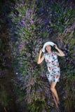 A mulher delgada romântica encontra-se no campo da alfazema fotografia de stock royalty free