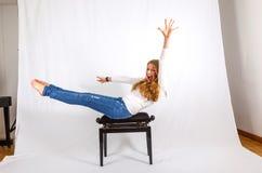 A mulher demonstra exercícios em uma cadeira do piano Imagens de Stock Royalty Free