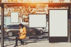 Mulher dentro da parada do ônibus com diversas bandeiras do modelo imagem de stock royalty free