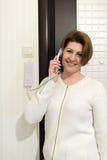 Mulher dentro do telefone de resposta home da segurança foto de stock