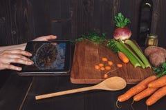 Mulher depois da receita na tabuleta e em cozinhar a refeição saudável na cozinha, cortando vegetais na tabela de madeira Imagens de Stock Royalty Free