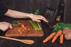 Mulher depois da receita na tabuleta e em cozinhar a refeição saudável na cozinha, cortando vegetais na tabela de madeira Fotos de Stock Royalty Free