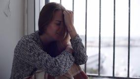Mulher deprimida que senta-se pela janela com chuva vídeos de arquivo