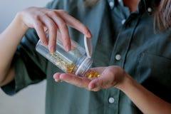 A mulher derrama fora dos comprimidos de um frasco com óleo de fígado de bacalhau imagens de stock royalty free