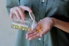 A mulher derrama fora dos comprimidos de um frasco com óleo de fígado de bacalhau imagem de stock