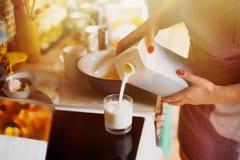 A mulher derrama o leite em um vidro Foto de Stock Royalty Free