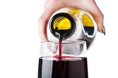 A mulher derrama o vinho em um vidro Imagem de Stock Royalty Free