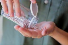 A mulher derrama os comprimidos brancos de um frasco transparente em sua mão imagem de stock