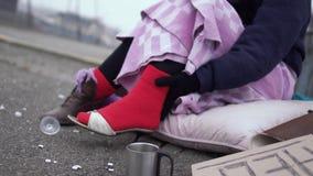 A mulher desabrigada aprecia as sapatas vestidas em uma peúga vermelha grossa fora vídeos de arquivo