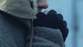 A mulher desabrigada miserável em sujo fecha o aquecimento de suas mãos congeladas, pobreza filme