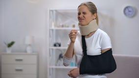 Mulher desagradada no colar cervical da espuma e no telefone de fala do estilingue do braço, más notícias vídeos de arquivo