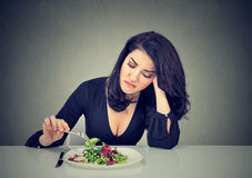 Mulher desagradada que come a alface de folha verde cansado de limitações da dieta Fotografia de Stock Royalty Free