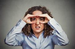 A mulher desagradada que olha através dos dedos gosta de binóculos Fotos de Stock Royalty Free