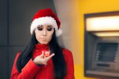 Mulher desapontado com caixa de presente pequena na frente de um ATM imagem de stock royalty free