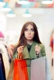 Mulher desapontado da compra que veste um revestimento verde na loja da forma foto de stock